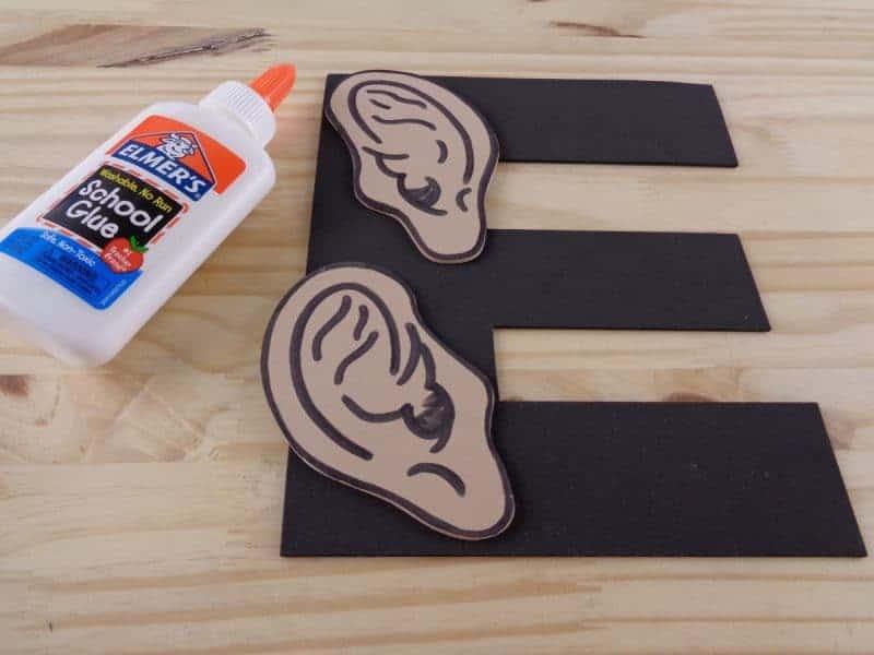 Glue the ears onto the letter E.