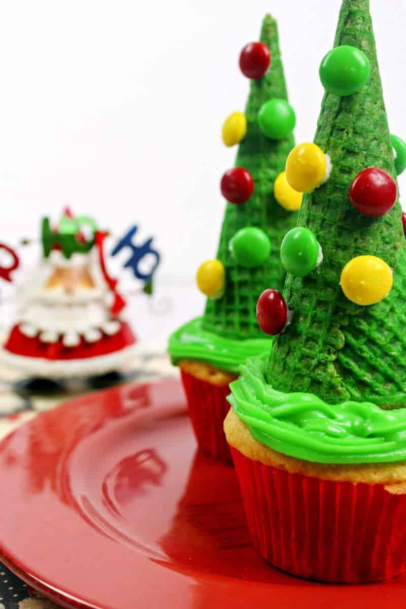 These fun Christmas tree cupcakes are easy to make by topping cupcakes with sugar cones and then decorating them with M&Ms as ornaments.