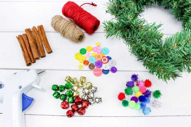 A fun DIY Christmas Tree Ornament craft, made using wreath garland, cinnamon sticks, twine, buttons, pom poms and jingle bells.