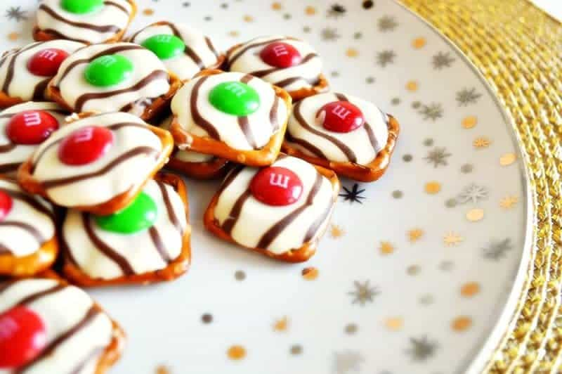 Salty-sweet Christmas pretzel hugs treats are quick and easy to make with just 3 ingredients: square pretzels, M&Ms, and Hershey's Hugs.