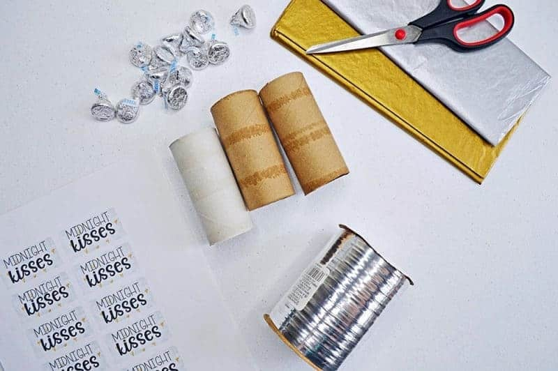 This fun Midnight Kisses New Year's Eve Party Poppers craft is easy to make with toilet paper rolls, tissue paper, ribbon, and the included printable label.