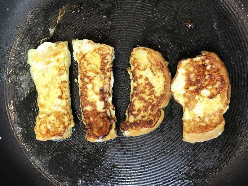 Heat a skillet over medium heat and grease with butter. Cook the French toast sticks until golden brown on both sides.