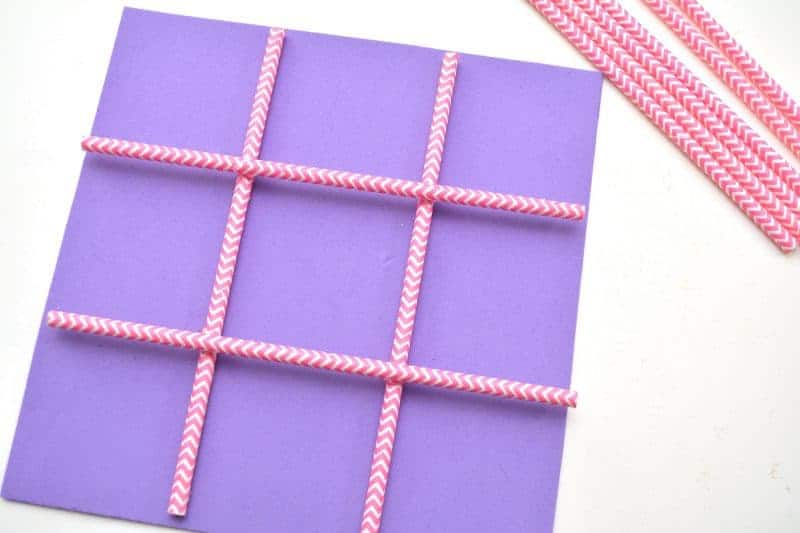 This DIY Tic Tac Toe board game is an easy Valentine's Day homemade craft for the kids to make using a foam sheet, paper straws, and pink and red hearts.