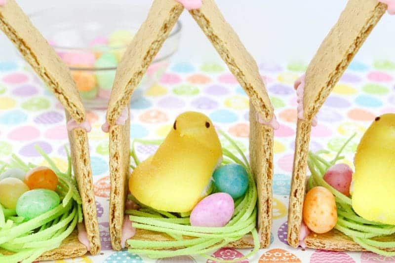 Peeps chicks houses are a fun no bake Easter treat perfect for the kids this Spring season. Made using Peeps Chicks, graham crackers, egg candies, and edible grass, this cute Easter recipe is perfect to make with the little ones.