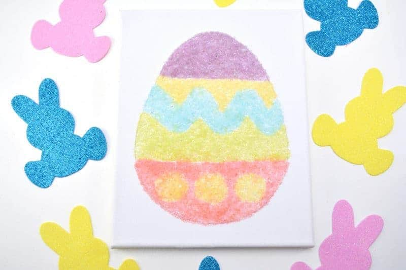 Salt glitter is fun to make and use in arts & crafts projects like this colorful salt glitter Easter egg canvas. Find out how to make homemade salt glitter with this step-by-step tutorial.