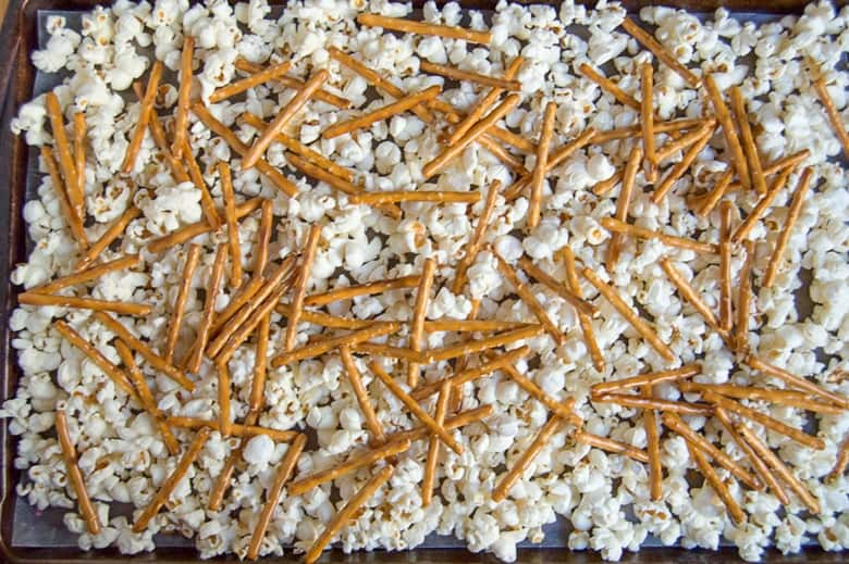 popcorn and pretzels spread out on lined baking sheet