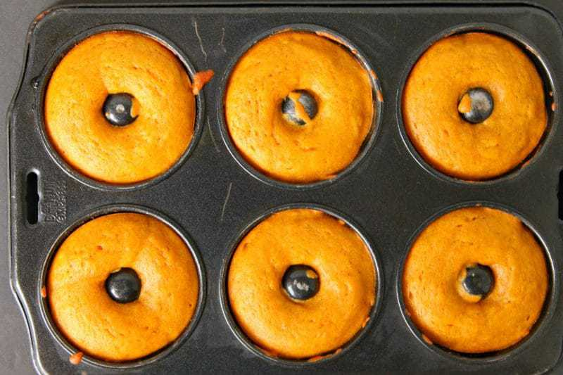 Baked pumpkin doughnuts served warm and smothered with glaze are the perfect Fall recipe for breakfast and dessert alike.