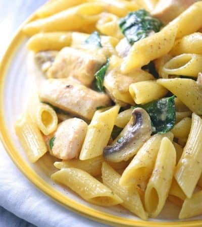 This creamy one-pot chicken pasta recipe takes just 30 minutes to cook. With spinach, mushrooms, and a creamy sauce, everyone in the family will love this easy one-pot meal.