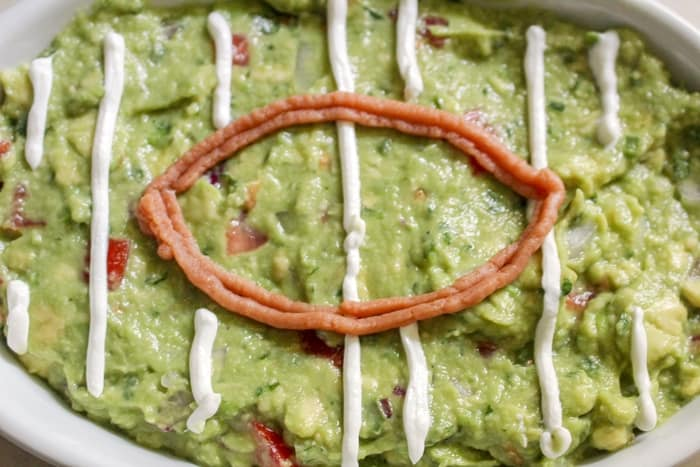 Spoon sour cream into a plastic baggie and cut a very small hole in the corner. Use baggie to pipe sour cream onto guacamole to make yard lines.