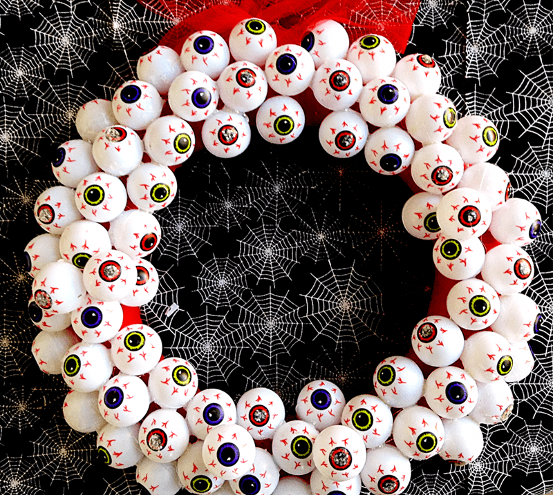 "Add a little bit of Halloween flair to your front door with this easy-to-make ""always watching"" creepy eyeball DIY Halloween wreath."