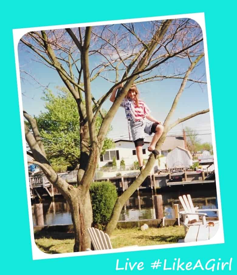 Young girl, about age 10, climbing on a tree branch in a backyard.