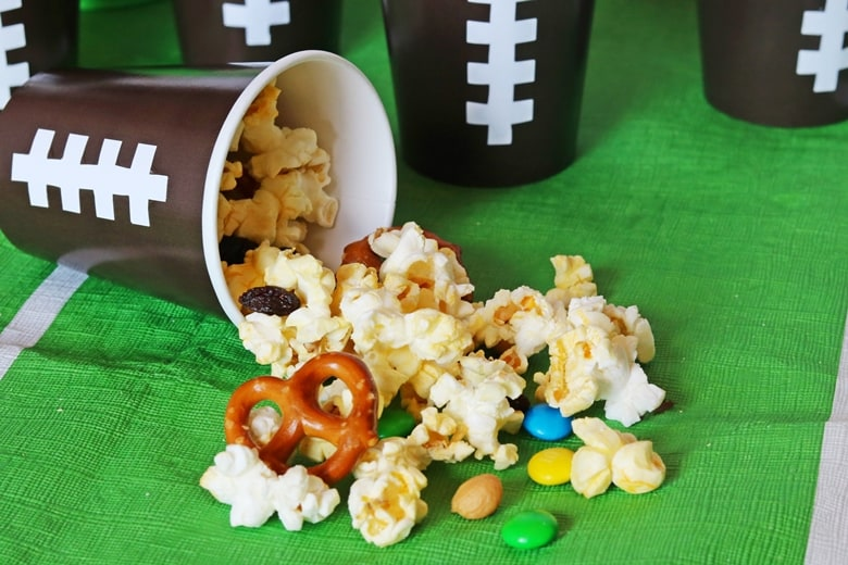 Game Day Snack Mix pouring out of brown cup and onto the table