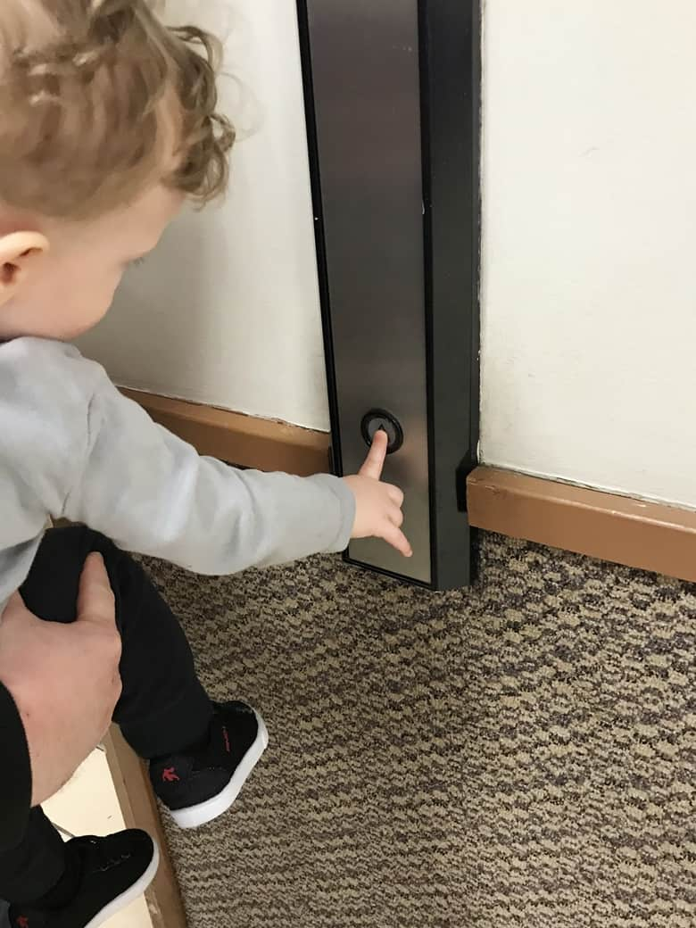 Toddler pressing elevator button