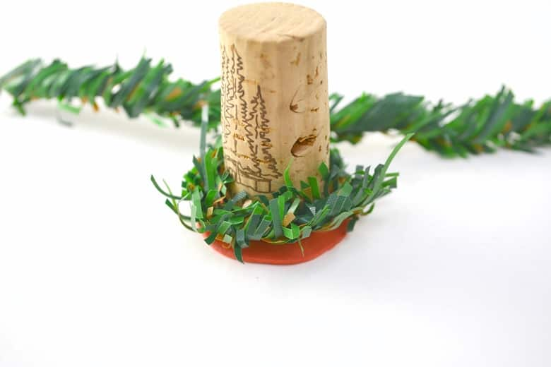 wine cork wrapped with a length of artificial pine garland