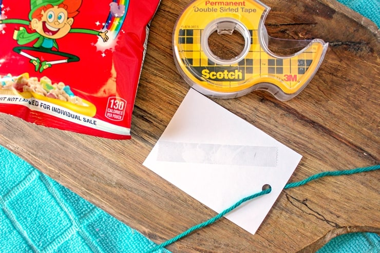A gift tag turned over with tape on the back and yarn through the hole on top. Roll of double sided tape and a bag of Lucky Charms can be seen next to the tag.