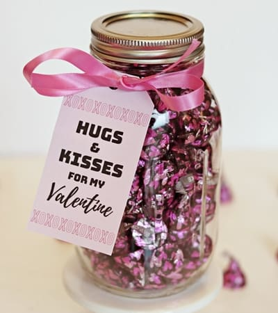 "An easy mason jar Hershey Kisses Valentine gift tutorial, complete with a printable ""hugs and kisses for my Valentine"" tag."