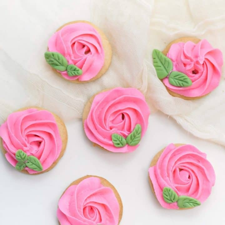 sugar cookies decorated to look like roses using pink icing and green fondant