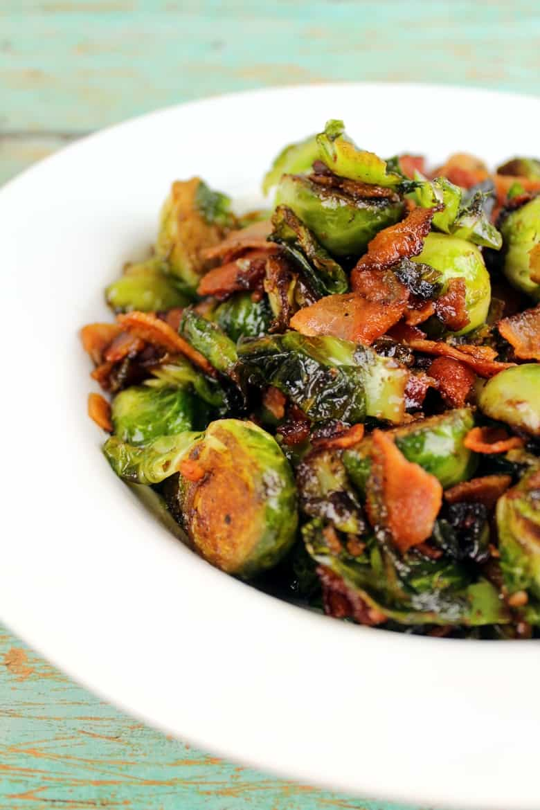 Brussel Sprouts with Bacon and Balsamic Reduction in a white bowl on a wooden table