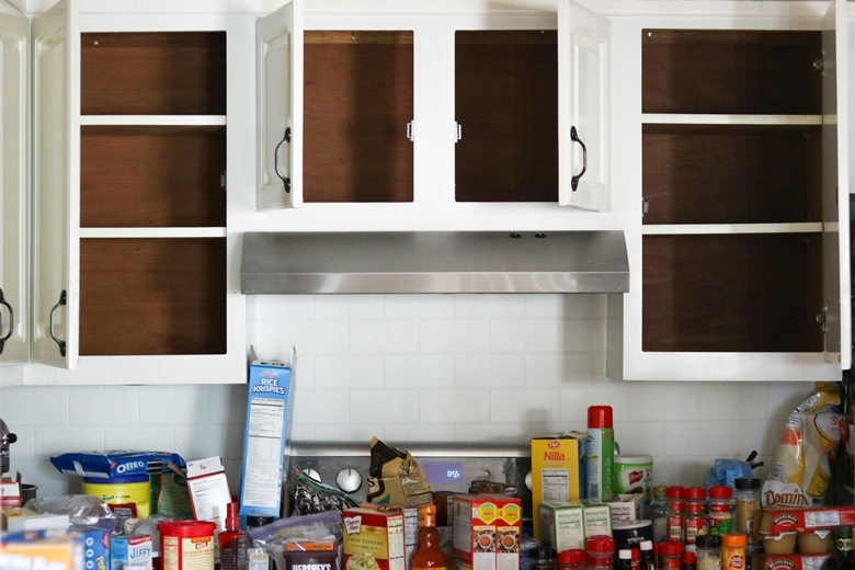 Empty cabinets with a lot of pantry items removed and placed on countertop underneath