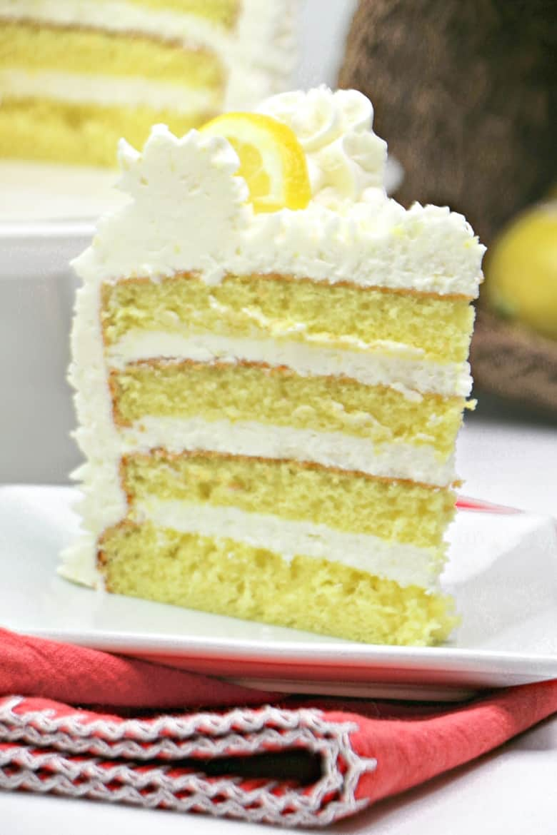 A slice of 4-tier lemon layer cake with lemon frosting and garnished with lemon slices.