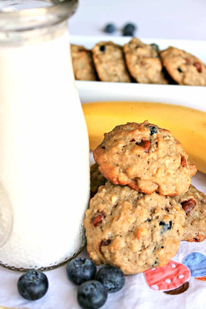 Breakfast Cookies next to a glass of milk, with fresh blueberries around them.