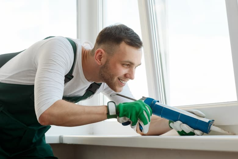 Man caulking around a window