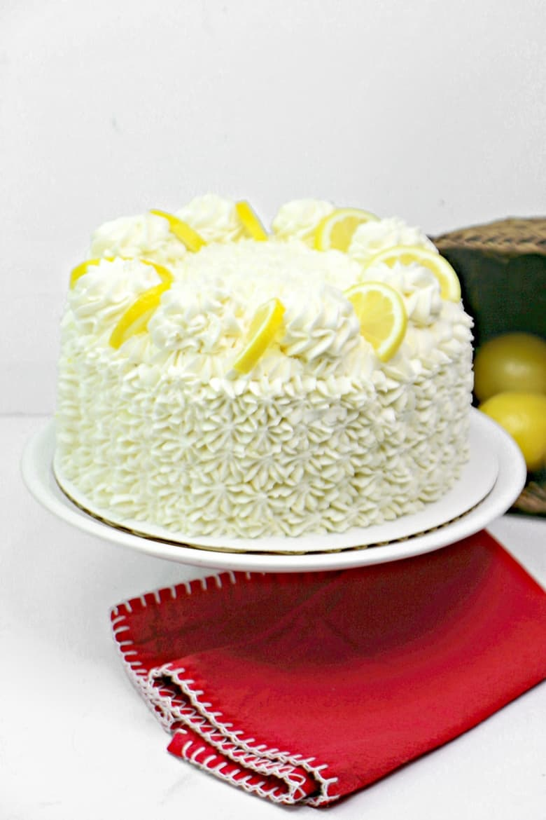 Lemon cake covered with white frosting and garnished with dollops of frosting and lemon garnishes.