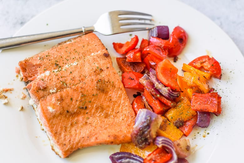Salmon filet, peppers, and onions on a white plate with a fork.
