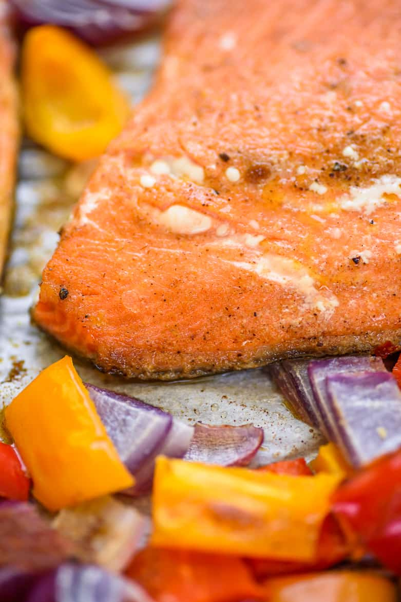 Chili lime salmon filet, peppers, and onions on sheet pan
