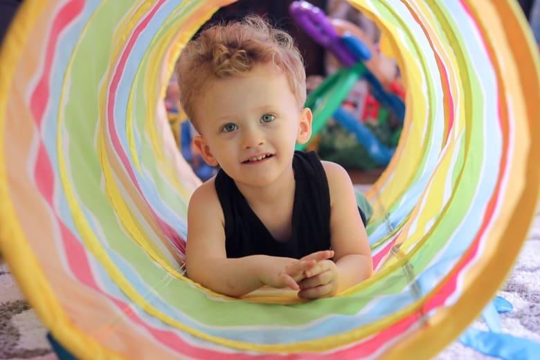 Toddler boy crawling through toy tunnel