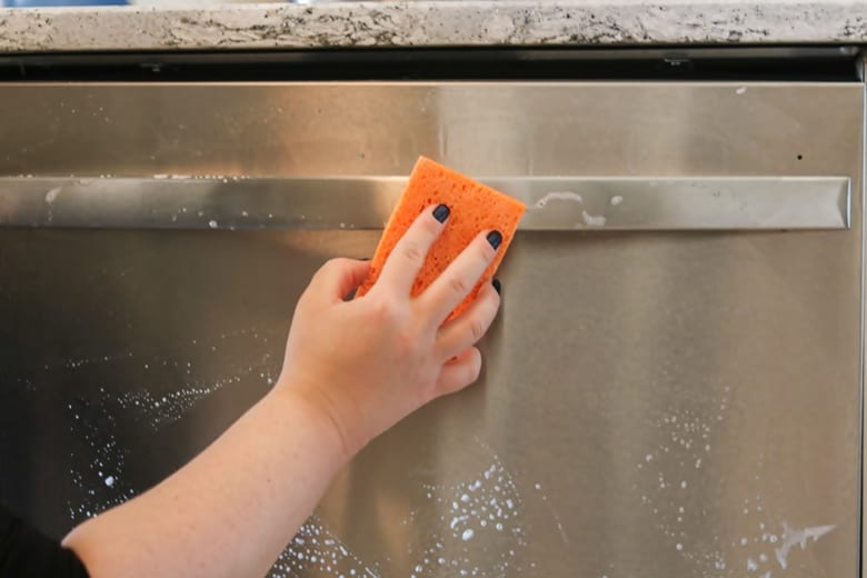 A hand holding a sponge and wiping a sudsy stainless steel dishwasher handle