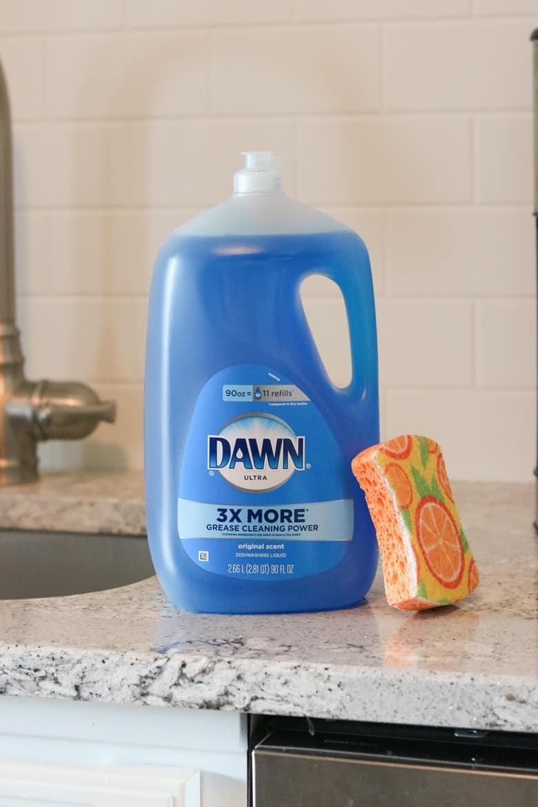 Dawn Ultra dish soap and orange sponge on kitchen countertop