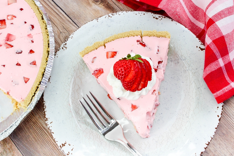 Slice of Strawberry Jello Pie on white plate, garnished with whipped cream and strawberries