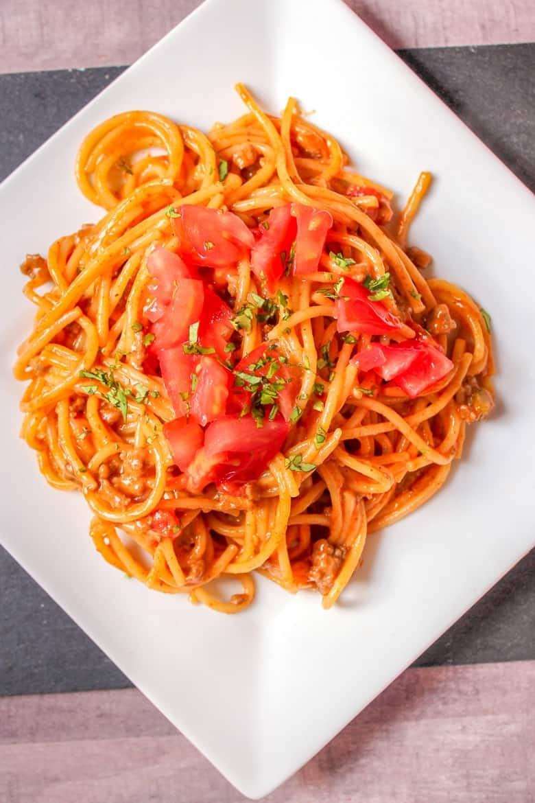 Taco spaghetti topped with tomatoes and cilantro