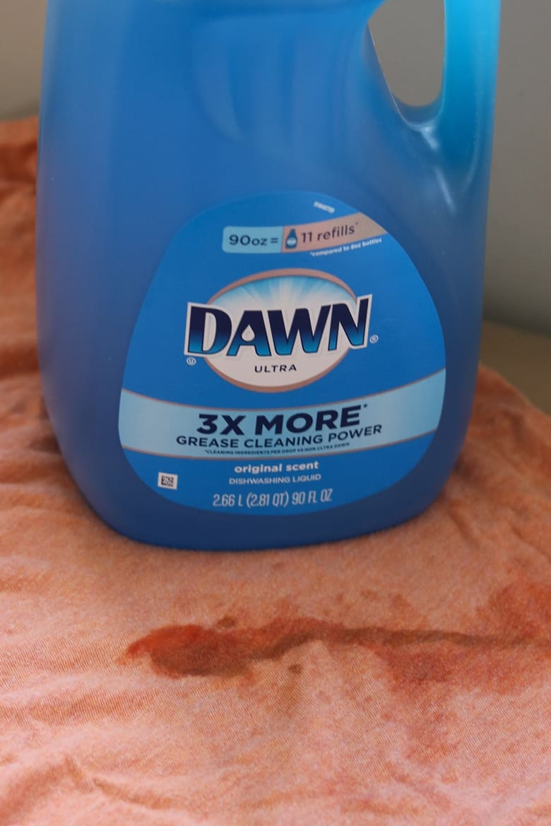 Container of blue Dawn dish soap on top of a stained orange shirt