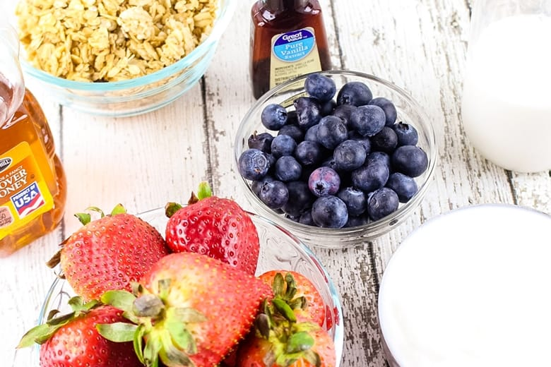 A bottle of vanilla extract and bowls of granola, blueberries, milk, yogurt, and strawberries.