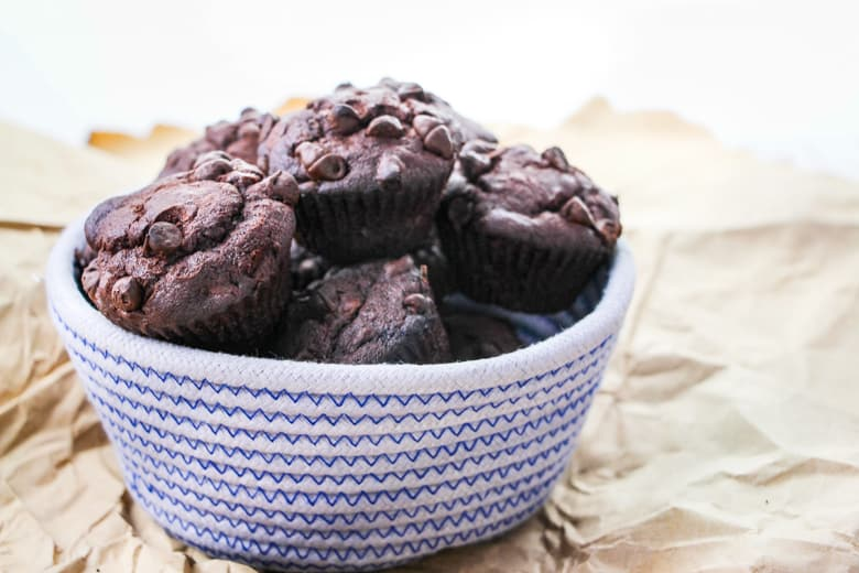 Blue and white woven bowl filled with chocolate muffins with chocolate chips