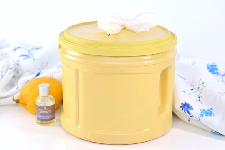 DIY Cleaning Wipes in yellow container with lavender essential oil and a lemon next to them