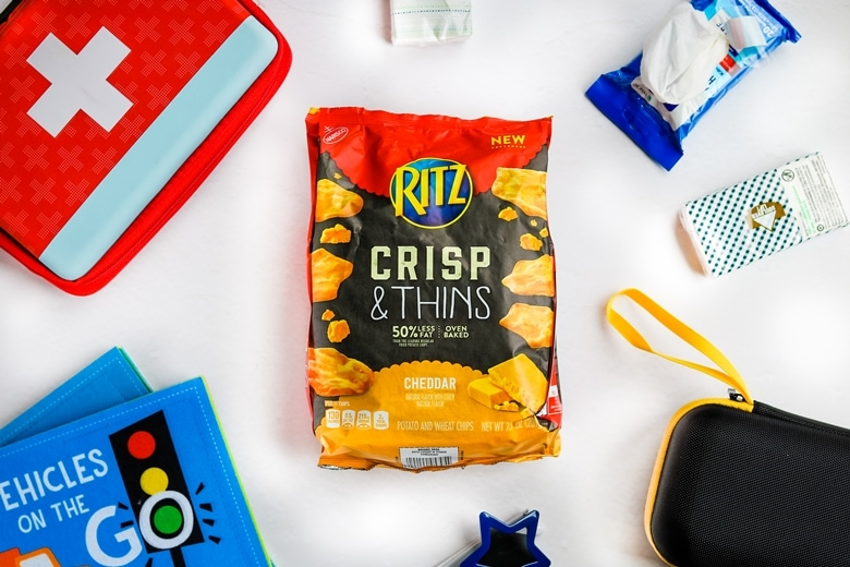 RITZ Crisp & Thins, travel size tissue pack, sunglasses, kids activity books, car emergency kit, and hand wipe