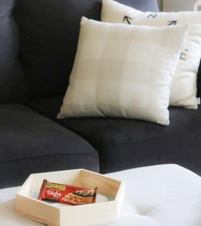 Tray with snack on ottoman, with couch in background