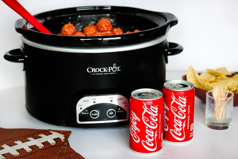Crockpot Meatballs with Coca-Cola served in crockpot with cans of coke and chips