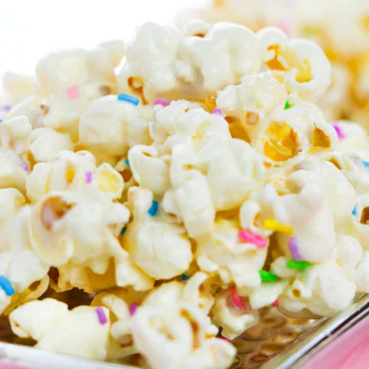 Cake batter popcorn topped with rainbow sprinkles and served on a flat silver plate.