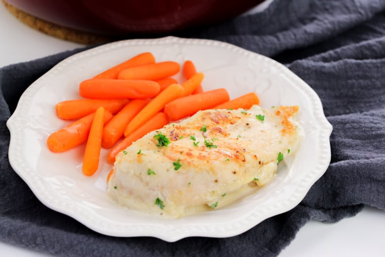 Creamy Garlic Chicken and carrots on white plate with dark blue napkin