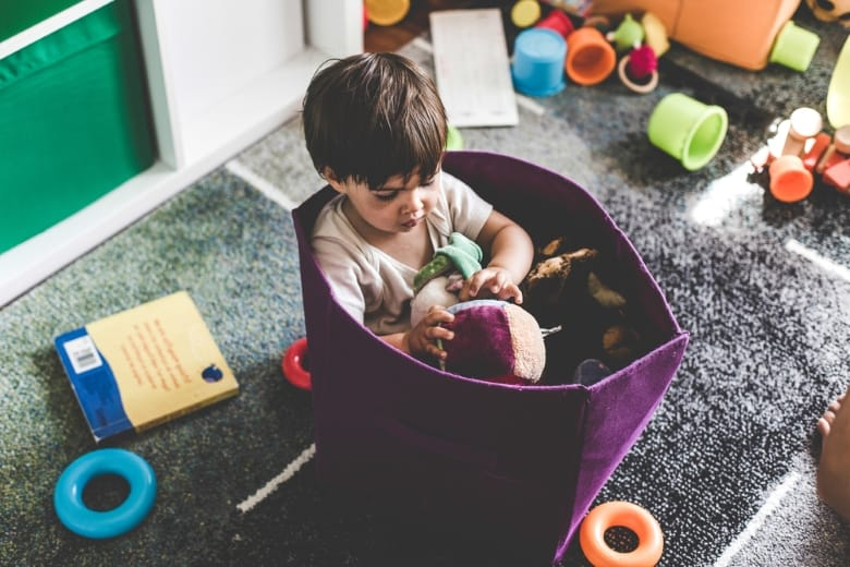 Child sitting in a storage container playing with toys
