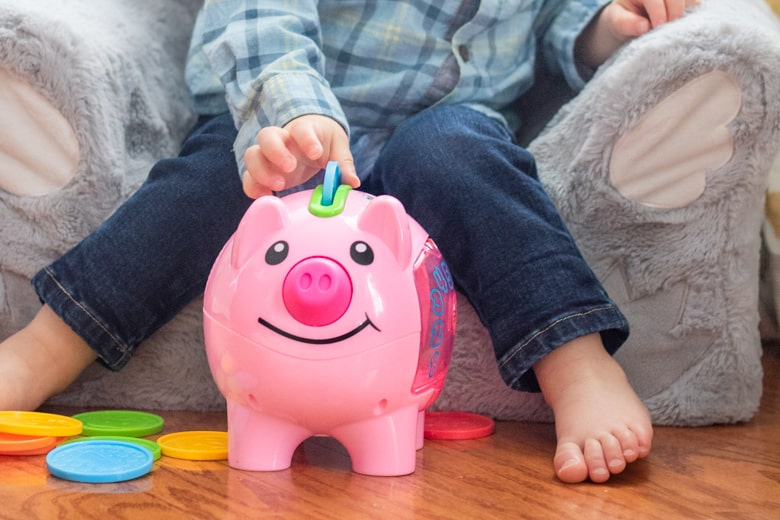 Toddler putting plastic coin in pink piggy bank