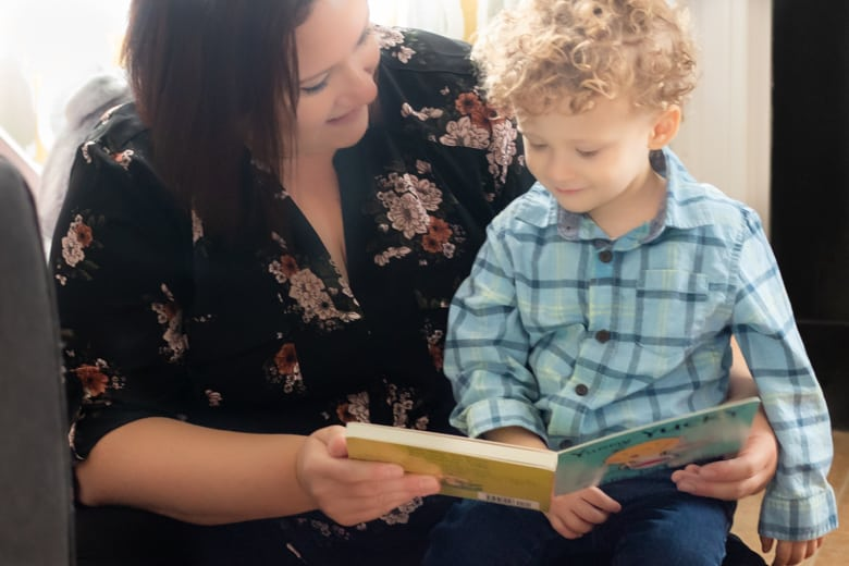 Mom reading book with toddler son