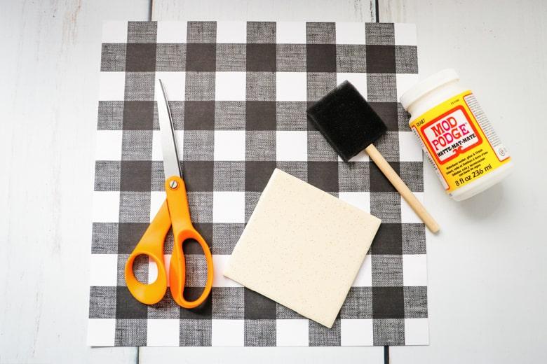 Scissors, ceramic tile, foam brush, and Mod Podge on top of 12 x 12 piece buffalo check pattern scrapbook paper
