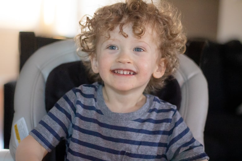 Smiling 2-year-old boy sitting in a high chair