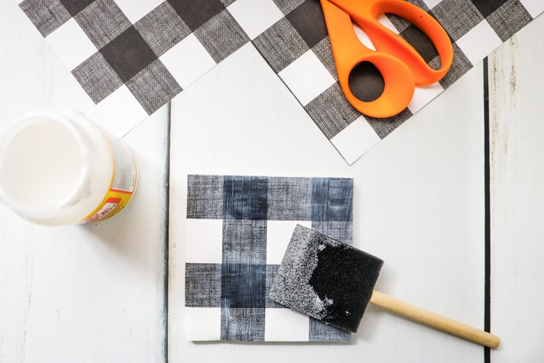 Foam brush applying Mod Podge on top of scapbook paper