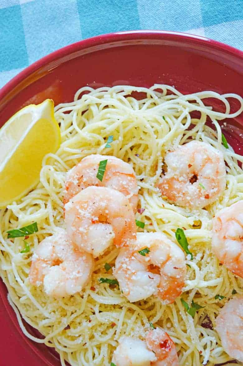 shrimp scampi over angel hair pasta served with a lemon wedge and topped with parsley
